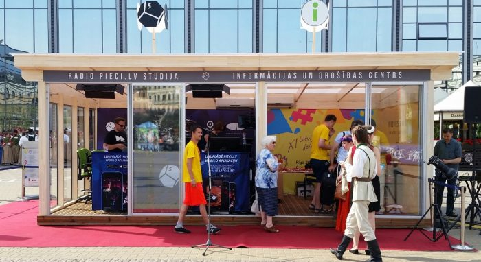 OBICONVERANDA at Station square for the Song and Dance festival as the official info point and Latvias Radio 5 — Pieci.lv studio.